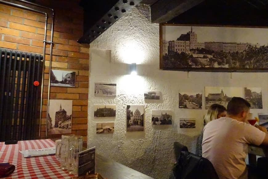 Fotografie dawnego Kołobrzegu zdobiące ściany w browarze– restauracji Colberg w wieży ciśnień w Kołobrzegu. Zdjęcie Barbara Jakimowicz-Klein. Blog SunSeasons24